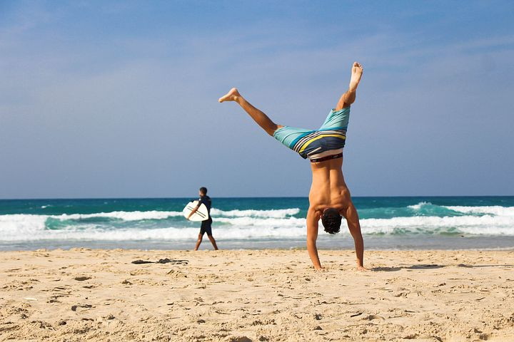 Fit guy doing cartwheels on the beach