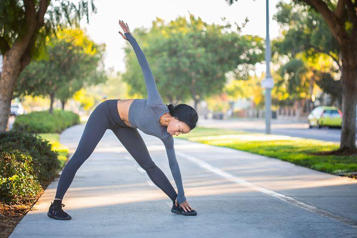 Fit woman stretching on sidewalk