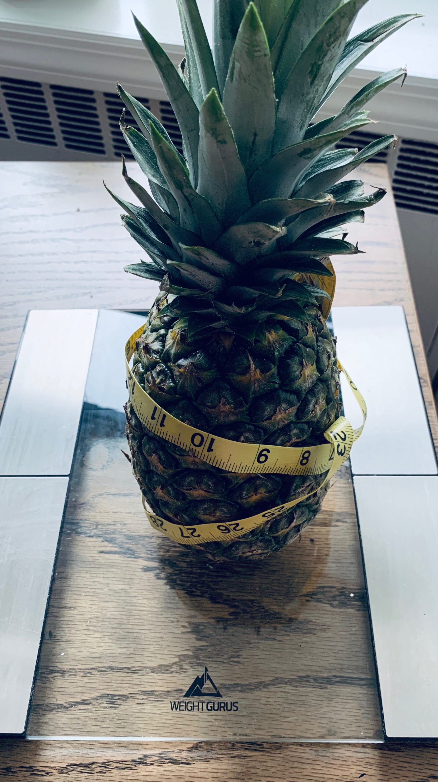 Pineapple on scale with tape measure around it