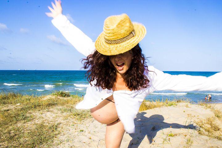 Pregnant woman enjoying the beach on a sunny day
